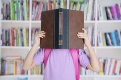 Podstawowe studenckie kryjówki jej twarz za książką fotografia royalty free