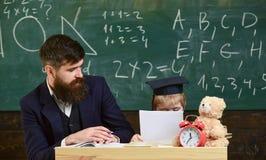 Podstawowej edukaci pojęcie Ojciec uczy synowi podstawową wiedzę, dyskutuje, wyjaśnia, Nauczyciel wewnątrz i uczeń zdjęcie royalty free