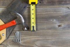 Podstawowi dom naprawy narzędzia na wietrzejącym drewnie Zdjęcia Stock