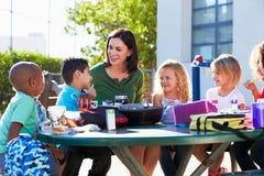 Podstawowi ucznie I nauczyciela łasowania lunch Obrazy Royalty Free
