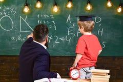 Podstawy edukaci pojęcie Chłopiec, dziecko w magisterskich nakrętek spojrzeniach przy skrobaninami na chalkboard podczas gdy nauc zdjęcia stock