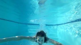 Podwodny dopłynięcie, dziewczyn skok do wody w basen i pławik z otwartymi oczami w czystej wodzie, zbiory
