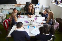 Podwyższony widok żeński szkoła podstawowa nauczyciela obsiadanie przy stołem ono uśmiecha się w sali lekcyjnej z uczniami podcza zdjęcia stock