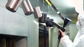 Poederdeklaag van metaaldelen Een mens in een beschermende kostuumnevels poedert verf van een kanon op metaalproducten stock videobeelden