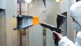 Poederdeklaag van metaaldelen Een mens in een beschermende kostuumnevels poedert verf van een kanon op metaalproducten stock footage