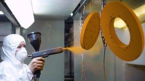 Poederdeklaag van metaaldelen Een vrouw in een beschermende kostuumnevels poedert verf van een kanon op metaalproducten stock video