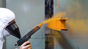 Poederdeklaag van metaaldelen Een vrouw in een beschermende kostuumnevels poedert verf van een kanon op metaalproducten stock footage