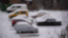 Poedersneeuw die op achtergrond van vage parkerenplaats vallen stock video