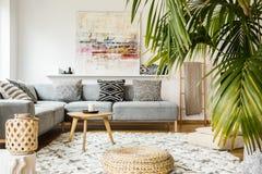 Poef en houten lijst in moderne woonkamer met hierboven het schilderen stock afbeeldingen