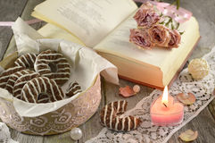 Poem book with burning candle. Still life with home made cookies, burning candle, poem book and bunch of roses Royalty Free Stock Photography