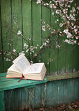 Poem book on green bench with cherry tree Stock Images