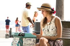 Poems for strangers at Pike Market, Seattle. Seattle, Washington, USA - September 4th, 2017: A young woman is writting poems for customers with a typewriter in Stock Photography