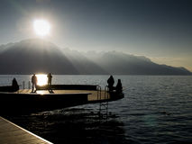 Poeple on a platform. Platform with people against sunlight above a lake Stock Photography