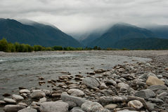 Poerua River and mountains in the clouds Stock Photos