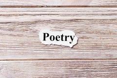 Poesía de la palabra en el papel Concepto Palabras de la poesía en un fondo de madera imagen de archivo