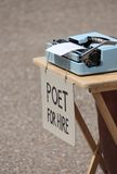 Poet for hire with typewriter. And sign stock photo