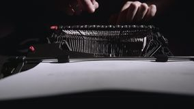 Poet types the text of the poem on a retro typewriter. Sitting at the table in the evening stock video footage