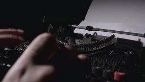 Poet types the text of the poem on a retro typewriter. Sitting at the table in the evening stock footage