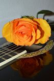 Poetry and music, close-up. Beautiful yellow rose making contrast with a black guitar, expressing love songs and love poetry stock images