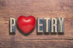 Poetry heart wooden. Poetry word combined on vintage varnished wooden surface with heart symbol inside royalty free stock photos