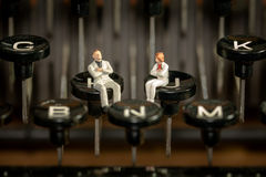 Poets and author writing crisis. Concept with 2 miniatures sitting on a type machine waiting for new ideas Stock Images