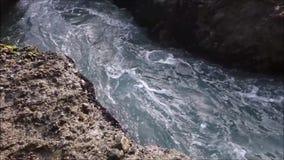 Pofalowane ocean wody pieścą skalistego brzeg zbiory wideo