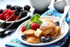 荷兰微型薄煎饼叫poffertjes用莓果 免版税库存图片