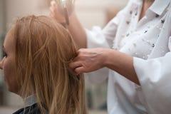 Pofile kvinna i salong och frisör med en hårtork royaltyfria foton