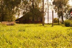 Pogodna lato łąka przed wioska domem Zdjęcia Royalty Free