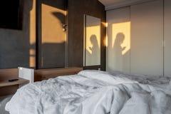 Pogodna sypialnia w nowożytnym stylu z szarości ścianą obraz stock