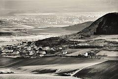 Pogodny światło w Czeskich środkowych górach kształtuje teren teren z Rana wioską na przedpolu i Louny miastem na tle w zimy with Obrazy Stock