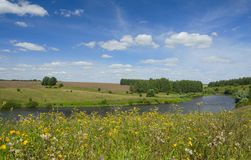Pogodny lato krajobraz z rzeką, polami, zielonymi wzgórzami i pięknymi chmurami w niebieskim niebie, obraz royalty free