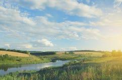 Pogodny lato krajobraz z rzeką, polami, zielonymi wzgórzami i pięknymi chmurami w niebieskim niebie przy zmierzchem, zdjęcia royalty free