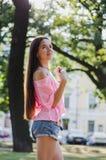 Pogodny lato portret elegancka modniś dziewczyna z długie włosy przy parkiem, uśmiechający się zabawę i mieć, odzieży lata menchi obraz stock
