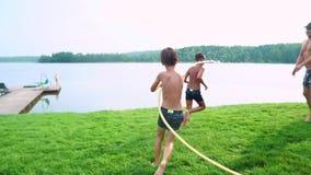 Pogodny letni dzień na gazon rodzinie z dwa dziećmi zabawę bawić się z wodnym i roześmianym Rozochocona atmosfera a zbiory