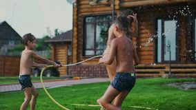 Pogodny letni dzień na gazon rodzinie z dwa dziećmi zabawę bawić się z wodnym i roześmianym Rozochocona atmosfera a zdjęcie wideo
