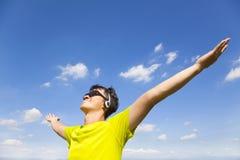 Pogodny młody człowiek cieszy się muzykę z niebieskim niebem Obraz Royalty Free