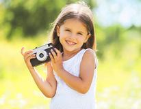 Pogodny portret śliczny uśmiechnięty małej dziewczynki dziecko z starą kamerą Zdjęcie Royalty Free