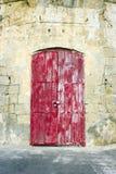 Pogodowy czerwony drzwi w wapnia budynku Zdjęcie Royalty Free