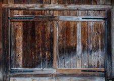 Pogody będący ubranym drewniani drzwi na drewnianym panelu budynku Obrazy Stock