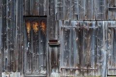 Pogody będący ubranym drewniani drzwi na drewnianym panelu budynku Zdjęcia Royalty Free