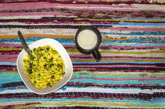 Poha(Pounded paddy) and coffee. Bowl of poha(Flattened rice/beaten rice/Pounded paddy) and a mug of coffee on colorful rug, top view Stock Photos