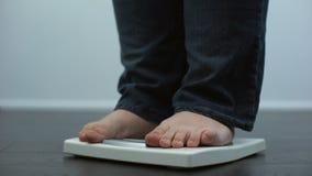 Poids corporel de vérification masculin dodu sur des échelles, désordre de santé, résultat de manger avec excès banque de vidéos