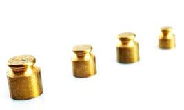 Poids de couleur d'or sur un fond blanc Photographie stock libre de droits