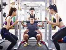 Poids de levage de jeune homme asiatique dans le gymnase Photographie stock