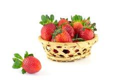 Poignée de fraises dans un panier en osier Photos stock