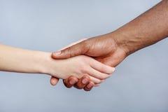 Poignée de main amicale par des personnes d'appartenance ethnique différente Photo stock