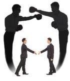 Poignée de main asiatique d'homme d'affaires avec l'ombre de combat Photographie stock