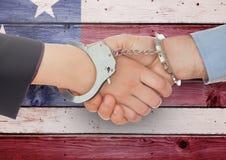 Poignée de main avec des menottes sur le fond en bois de drapeau américain Photographie stock libre de droits