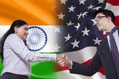 Poignée de main avec le drapeau de l'Inde et de l'Amérique Photos stock